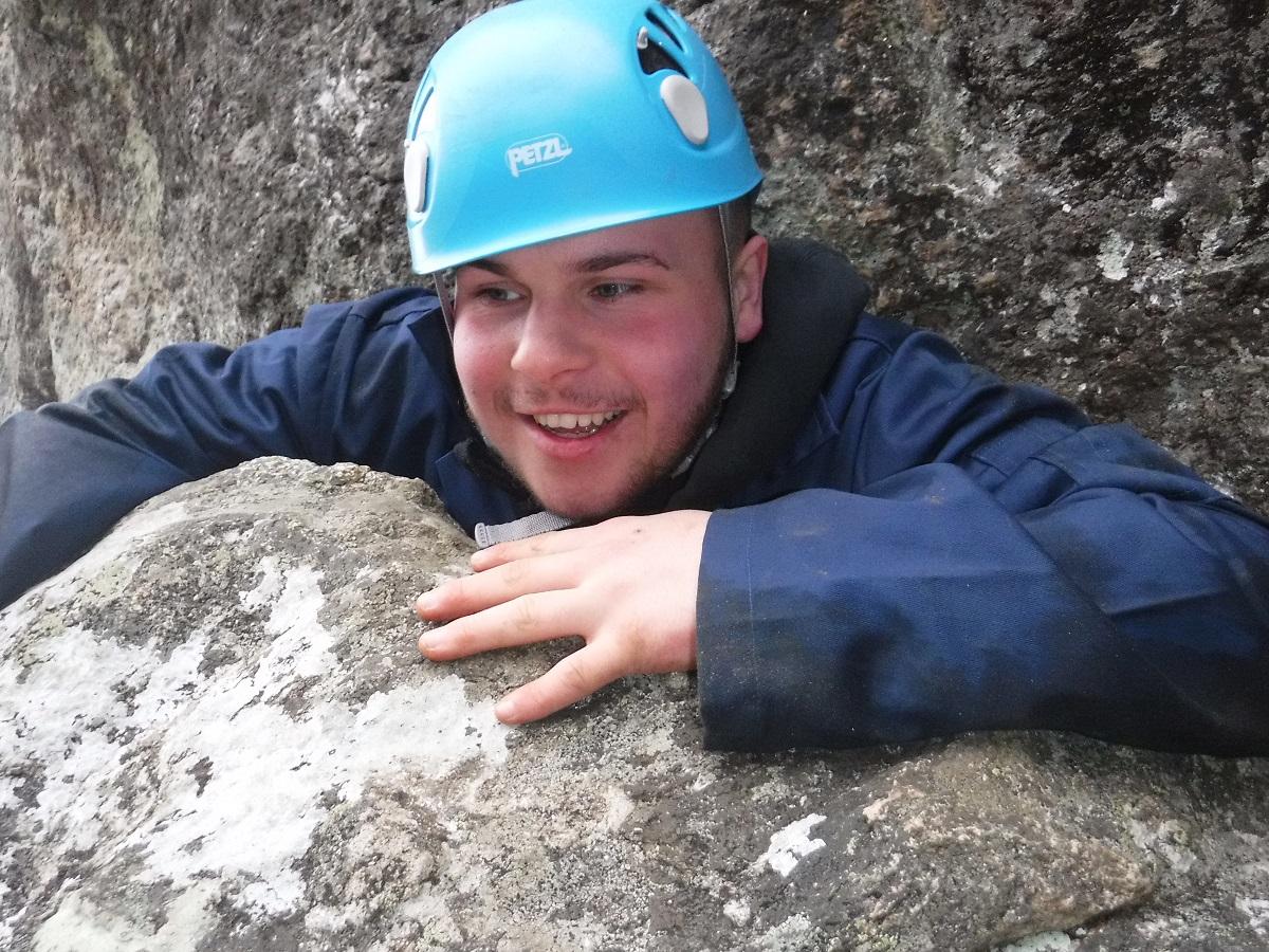 Young boy climbing through a narrow gap weasling
