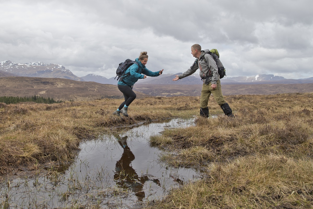 Client and guide on a days mountain guiding jumping over a puddle
